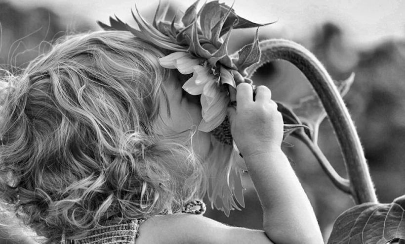 niña oliendo girasol