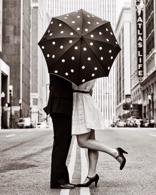 pareja besándose con paraguas
