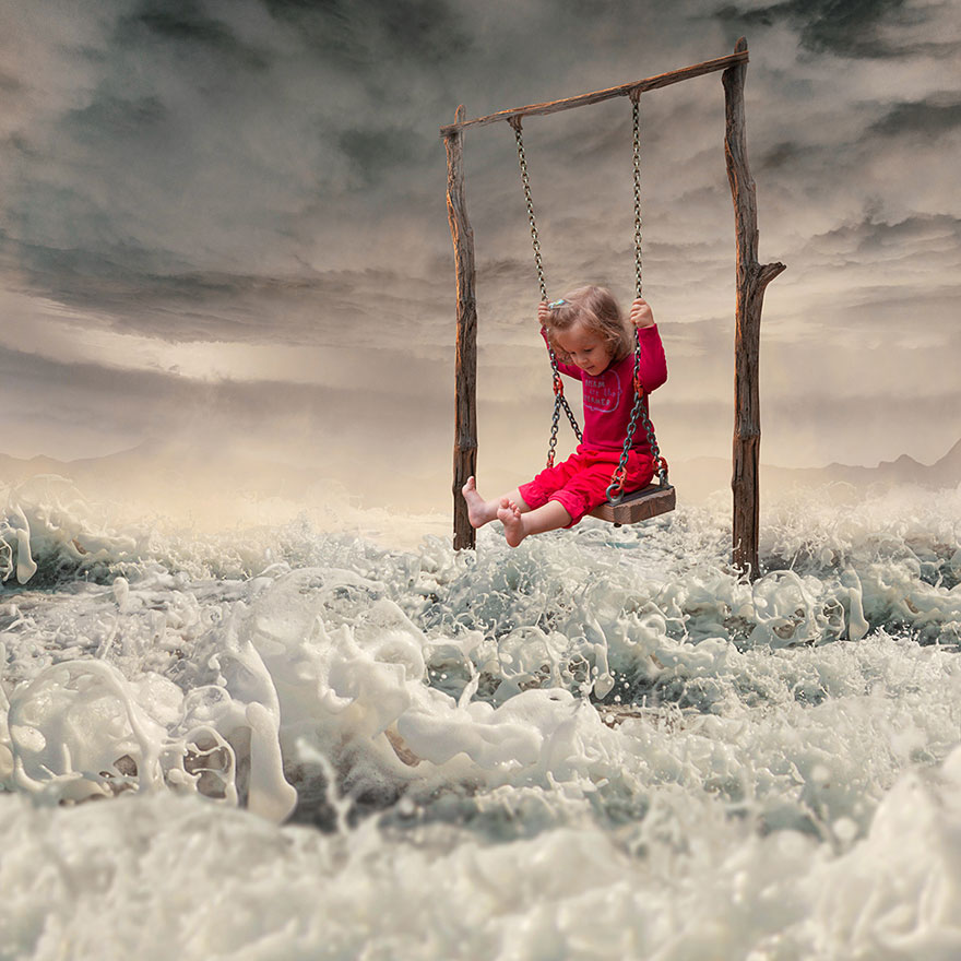 niña en columpio con mar