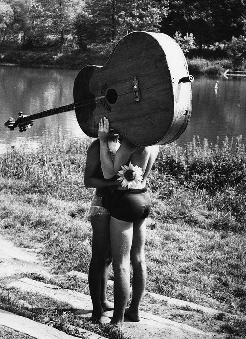 chicos con guitarra tapándolos el beso